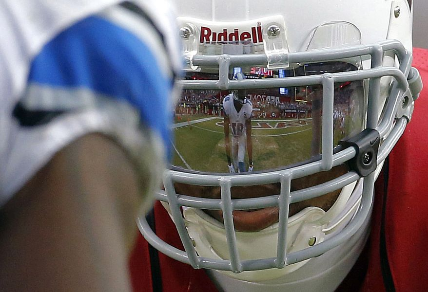 Detroit Lions wide receiver Calvin Johnson is reflected in the face mask of Arizona Cardinals defensive back Patrick Peterson during the second half of a NFL football game, Sunday, Sept. 15, 2013, in Glendale, Ariz. (AP Photo/Darryl Webb)