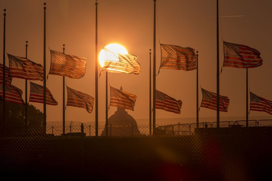 The flags surrounding the Washington Monument fly at half-staff as ordered by President Barack Obama following the deadly shooting Monday at the Washington Navy Yard, Tuesday morning, Sept. 17, 2013, in Washington. (AP Photo/J. Scott Applewhite)