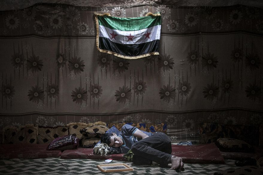 In this Tuesday, Sept. 17, 2013 photo, a Syrian opposition fighter rests inside a cave at a rebel camp in the Idlib province countryside of Syria. The main Syrian opposition coalition urged the international community to take swift action against the regime of President Bashar Assad in response to a U.N. finding that the nerve agent sarin was used in a deadly attack near the capital last month. (AP Photo)