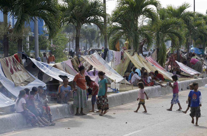Villagers fleeing the fighting between government forces and Muslim rebels occupy the center median of a boulevard in Zamboanga, Philippines, on Wednesday, Sept. 18, 2013. (AP Photo/Bullit Marquez)