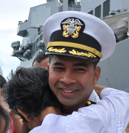 ** FILE ** U.S. Navy Cmdr. Michael V. Misiewicz, then commanding officer of the guided-missile destroyer USS Mustin, is greeted by a member of his family as the Mustin arrives in Sihanoukville, Cambodia, on Dec. 3, 2010. Cmdr. Misiewicz was arrested on Tuesday, Sept. 17, 2013, in Colorado and charged with conspiracy in a bribery scheme to reap millions of dollars in port contracts worldwide, according to prosecutors. (AP Photo/U.S. Navy, Mass Communication Specialist 3rd Class Devon Dow)