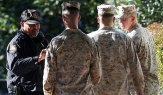 ** FILE ** Military personnel have their identification checked as they enter the Washington Navy Yard on Thursday, three days after a gunman opened fire inside a building and killed 12 people in September 2013. (Associated Press)