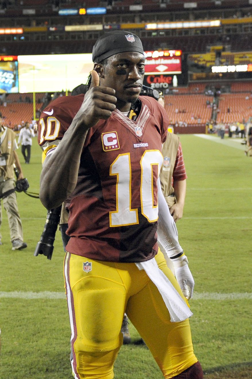 Washington Redskins quarterback Robert Griffin III flashes a thumbs up as he leaves the field after a NFL football game against the Philadelphia Eagles in Landover, Md., Monday Sept. 9, 2013. The Eagles defeated the Redskins 33-27. (AP Photo/Nick Wass)