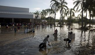 People wade through waist-high water in a store's parking, looking for valuables, south of Acapulco, in Punta Diamante, Mexico, Wednesday, Sept. 18, 2013. (AP Photo/Eduardo Verdugo)