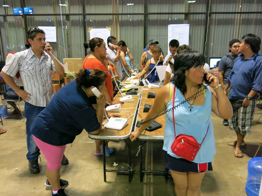 Residents of the storm-battered southern Mexican state of Guerrero use the courtesy phones provided at a temporary shelter in the Convention Center in Acapulco, Mexico, Thursday, Sept. 19, 2013. Hundreds were in the shelter, including several hundred from a village hit by a landslide Monday afternoon, where officials said at least 58 people were missing and presumed dead. (AP Photo/Michael Weissenstein)