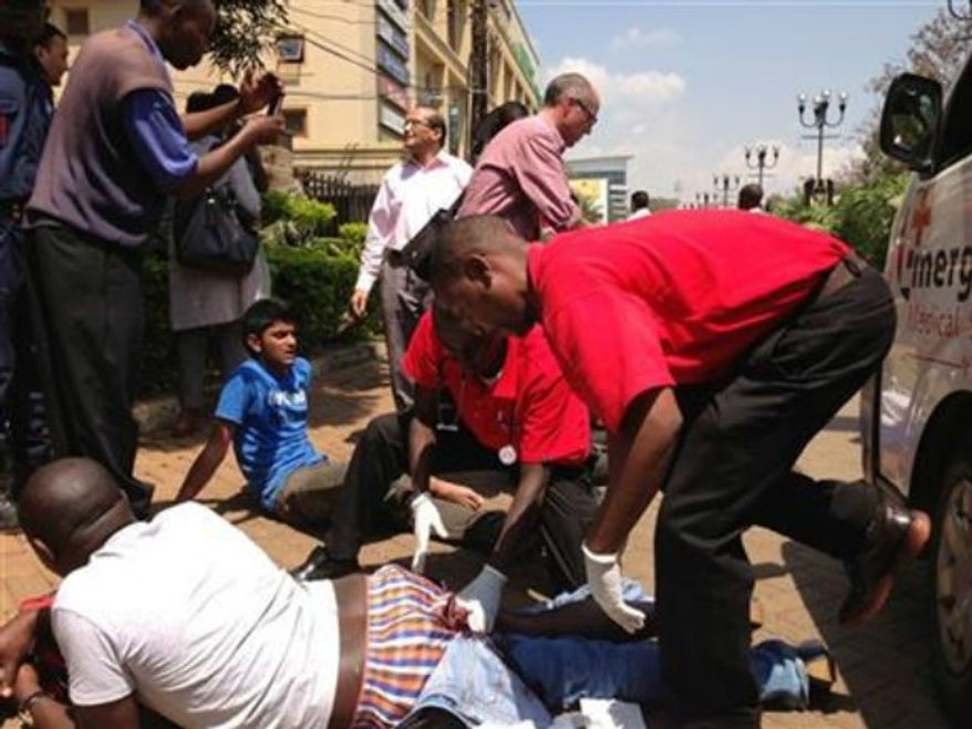 An injured man is treated outside an upscale shopping mall, seen background, in Nairobi, Kenya Saturday Sept. 21 2013, where shooting erupted when armed men attempted to rob a shop, according to police. Witnesses say a half dozen grenades also went off along with lobbies of gunfire that started at midday. (AP Photo/ Jason Straziuso)