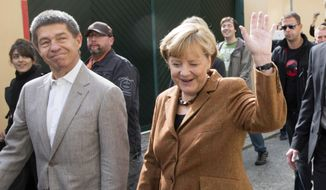 German Chancellor Angela Merkel, chairwoman of the Christian Democratic Union political party, waves to residents with her husband, Joachim Sauer (left), after they cast their votes in national elections in Berlin on Sunday, Sept. 22, 2013. Mrs. Merkel is running for her third term as chancellor. (AP Photo/Gero Breloer)