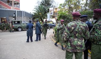 Security personnel take their positions on Sunday, Sept. 22, 2013, outside a shopping mall in Nairobi, Kenya,  where, authorities said, Islamic extremist attackers are holding an unknown number of hostages. (AP Photo/Sayyid Azim)
