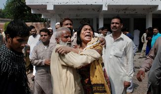 A Pakistani Christian woman mourns the death of her relatives at the site of a suicide attack on a church in Peshawar, Pakistan, on Sunday, Sept. 22, 2013. The bombing was in one of the worst assaults on the country's Christian minority in years. (AP Photo/Mohammad Sajjad)