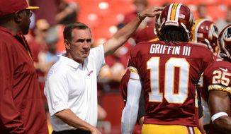 Washington Redskins head coach Mike Shanahan, left, greets Washington Redskins quarterback Robert Griffin III (10), right, before the Washington Redskins play the Detroit Lions in NFL football at FedExField, Landover, Md., Monday, September 9, 2013. (Andrew Harnik/The Washington Times)