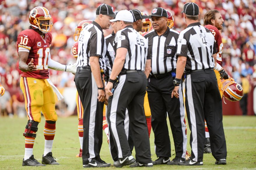 Referees talk after Washington Redskins quarterback Robert Griffin III (10) fumbles as he goes down after keeping the ball and rushing in the forth quarter as the  Washington Redskins play the Detroit Lions in NFL football at FedExField, Landover, Md., Monday, September 9, 2013. (Andrew Harnik/The Washington Times)