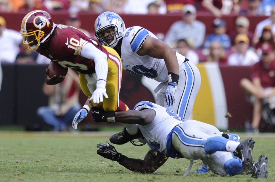Washington Redskins quarterback Robert Griffin III (10) is sacked by Detroit Lions defensive end Ezekiel Ansah (bottom) for a loss of 13 yards in the third quarter as the Washington Redskins play the Detroit Lions at FedExField, Landover, Md., September 22, 2013. (Preston Keres/Special for The Washington Times)