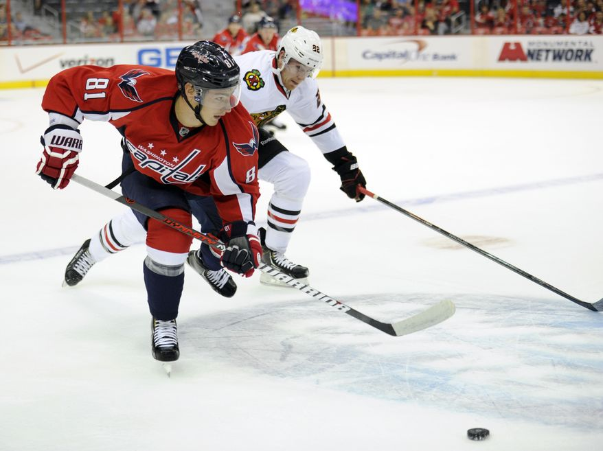 Washington Capitals defenseman Dmitry Orlov (81), of Russia, chases the puck against Chicago Blackhawks right wing Jimmy Hayes (22) during the first period an NHL preseason hockey game, Friday, Sept. 20, 2013, in Washington. (AP Photo/Nick Wass)