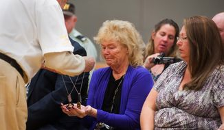 Peggy Eddington-Smith, 69, of Dayton, Nev., receives a reproduction copy of her father's dog-tags during a ceremony in Dayton, Nev., on Saturday, Sept. 21, 2013. (AP Photo/Kevin Clifford)