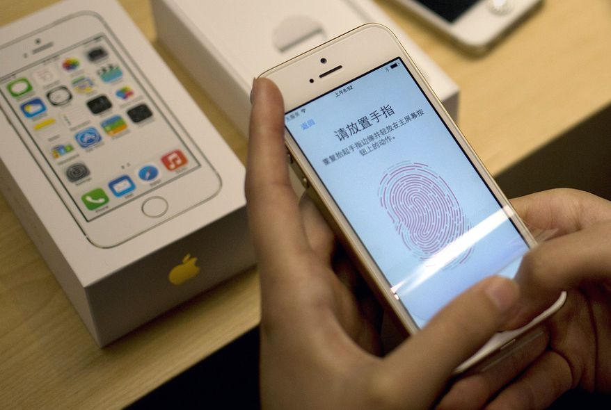 A customer configures the fingerprint scanner technology built into the Apple iPhone 5S at a company store in the Wangfujing shopping district of Beijing on Friday, Sept. 20, 2013. (AP Photo/Andy Wong)