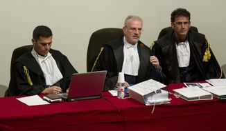 Court President, Judge Giovanni Puliatti, sitting at center, is flanked by judges Sergio Compagnucci, right, and Marco Mezzaluna, left, in the court room of the converted Teatro Moderno theater for his the trial of Captain Francesco Schettino, in Grosseto, Italy, Monday, Sept. 23, 2013. (AP Photo/Andrew Medichini)