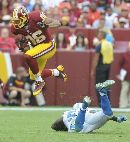 Washington Redskins tight end Jordan Reed leaps over Detroit Lions middle linebacker Stephen Tulloch during the second half of a NFL football game in Landover, Md., Sunday, Sept. 22, 2013. (AP Photo/Richard Lipski)
