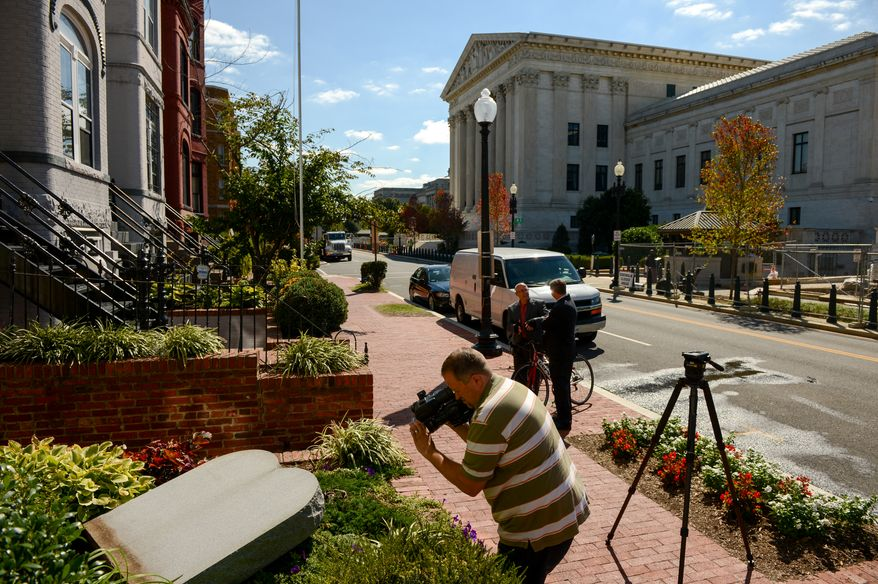A news camera man films a marble depiction of the ten commandments mounted in the front lawn of the Faith and Action offices after it was vandalized over the weekend across the street from the U.S. Supreme Court building, Washington, D.C., Monday, September 23, 2013. (Andrew Harnik/The Washington Times)