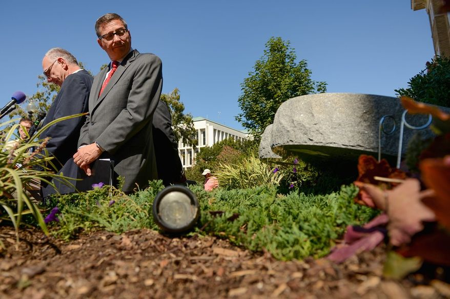 The Rev. Rob Schenck (right) of Faith and Action looks at the Ten Commandments sculpture that was knocked over by vandals. (Andrew Harnik/The Washington Times)