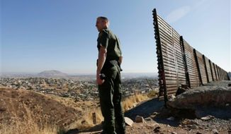 ** FILE ** U.S. Border Patrol agent Jerry Conlin looks out over Tijuana, Mexico, behind, along the old border wall along the U.S. - Mexico border, where it ends at the base of a hill in San Diego, June 13, 2013. (AP Photo/Gregory Bull, File)
