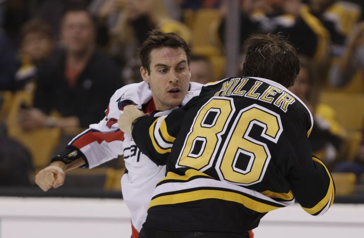 Boston Bruins defenseman Kevan Miller (86) fights Washington Capitals left wing Aaron Volpatti (24) during the first period of a hockey game, Monday, Sept. 23, 2013, in Boston. (AP Photo/Charles Krupa)