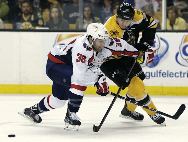 Washington Capitals defenseman Jack Hillen, left, tries to keep Boston Bruins right wing Nick Johnson, right, away from the puck during the second period of an NHL preseason hockey game, Monday, Sept. 23, 2013, in Boston. (AP Photo/Charles Krupa)
