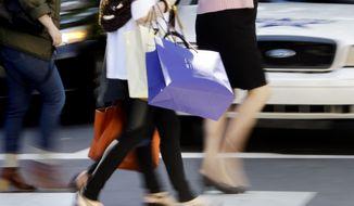 Pedestrians with shopping bags cross a street in Philadelphia on Wednesday, Sept. 18, 2013. (AP Photo/Matt Rourke)