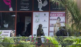 A Kenyan soldier prepares to enter the Westgate Mall, following a bout of heavy gunfire just after dawn, in Nairobi, Kenya Tuesday, Sept. 24, 2013. Kenyan security forces battled al-Qaeda-linked terrorists in an upscale mall for a fourth day Tuesday in what they said was a final push to rescue the last few hostages in a siege that has left at least 62 people dead. (AP Photo/Ben Curtis)