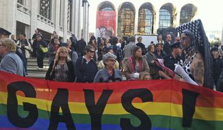 In this photo provided by Queer Nation NY, anti-Putin protestors demonstrate in front of the Metropolitan Opera at Lincoln Center in New York, where the Met held its season-opening gala featuring soprano Anna Netrebko and conductor Valery Gergiev, two longtime supporters of Russian President Vladimir Putin. Putin, who has upheld anti-gay laws passed by the Russian legislature, has denied that homosexuals face discrimination in Russia and said the law does not infringe on their rights. (Associated Press/Scott Wooledge, Queer Nation NY)