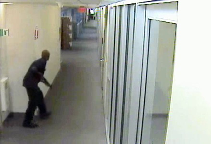 "** FILE ** Aaron Alexis was captured on video moving through the hallways of Building 197 at the Washington Navy Yard on Sept. 16 carrying a Remington 870 shotgun. FBI officials said he did not specifically target his shooting victims and was ""prepared to die."" (FBI via Associated Press)"