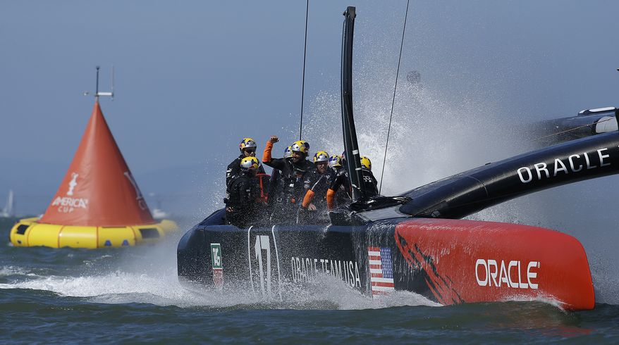 Oracle Team USA crosses the finish line during the 18th race of the America's Cup sailing event against Emirates Team New Zealand, Tuesday, Sept. 24, 2013, in San Francisco. Oracle Team USA won races 17 and 18 to pull even with Emirates Team New Zealand. (AP Photo/Ben Margot)