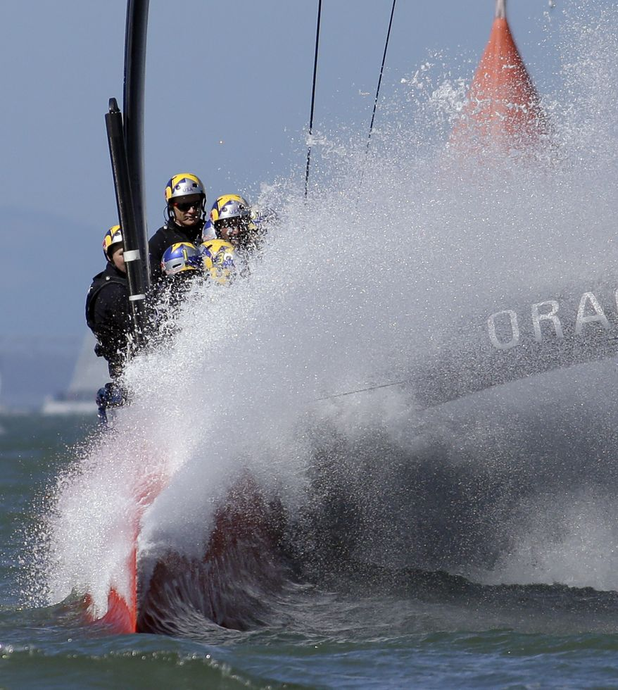 Oracle Team USA hits a wave during the 18th race of the America's Cup sailing event against Emirates Team New Zealand, Tuesday, Sept. 24, 2013, in San Francisco. Oracle Team USA won both races Tuesday, evening the series. (AP Photo/Ben Margot)