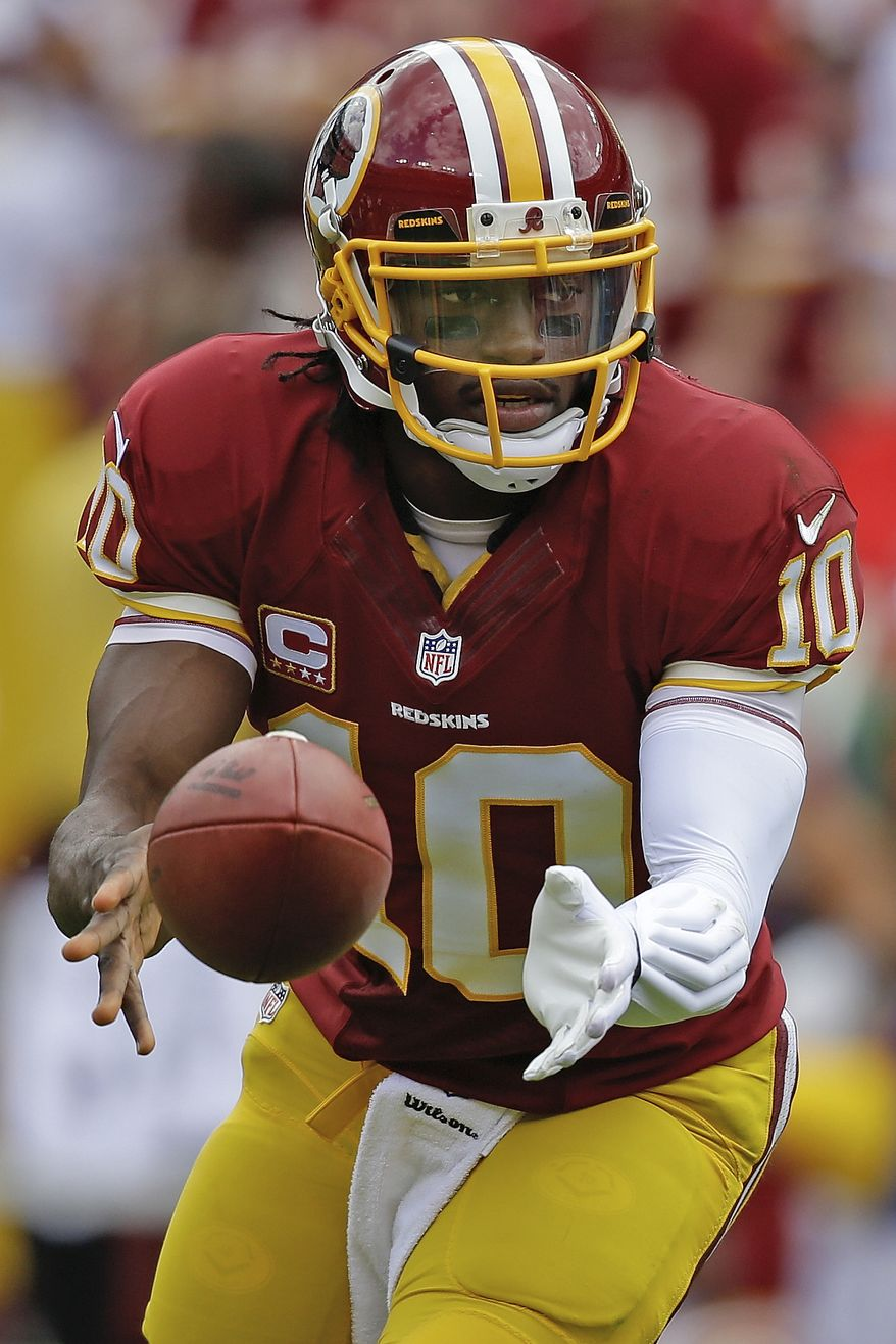 Washington Redskins quarterback Robert Griffin III hands off the ball during the first half of a NFL football game against the Detroit Lions in Landover, Md., Sunday, Sept. 22, 2013. (AP Photo/Alex Brandon)