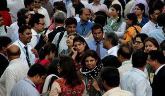 People rush out their offices after they felt a major earthquake that struck Baluchistan province in southwest Pakistan, 693 Kilometers (430 miles) from Karachi, Pakistan, Tuesday, Sept. 24, 2013. A deadly earthquake struck Tuesday in southwestern Pakistan sending poeople fleeing into the streets and praying for their lives as buildings swayed, officials said. (AP Photo/Shakil Adil)
