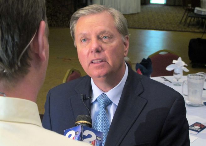 **FILE** Sen. Lindsey Graham talks Sept. 3, 2013, to a reporter following a speech to business leaders in Goose Creek, S.C. Graham is facing three challengers in the 2014 Republican primary for his seat. (Associated Press)