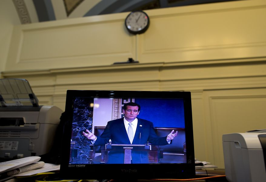Sen. Ted Cruz, R-Texas, is seen on a television screen in the Senate Press Gallery during the tenth hour of his speech on the Senate floor on Wednesday, Sept. 25, 2013, in Washington. Cruz began a lengthy speech urging his colleagues to oppose moving ahead on a bill he supports. The measure would prevent a government shutdown and defund Obamacare. (AP Photo/ Evan Vucci)