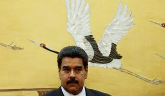 Venezuela's President Nicolas Maduro attends a signing ceremony with Chinese counterpart Xi Jinping, unseen, at the Great Hall of the People in Beijing Sunday, Sept. 22, 2013. (AP Photo/Lintao Zhang, Pool)