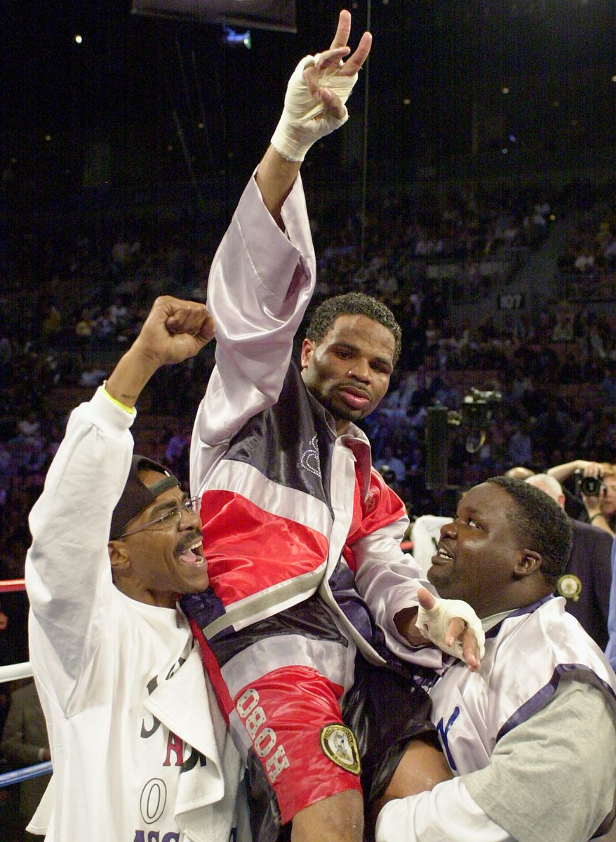 **FILE** William Joppy, of Silver Spring, Md., center, is raised aloft by his corner after he won the WBA middlweight championship bout against Howard Eastman, of England, at the Mandalay Bay resort in Las Vegas, Saturday, Nov. 17, 2001. Joppy won the fight by decision. (AP Photo/Mark J. Terrill)