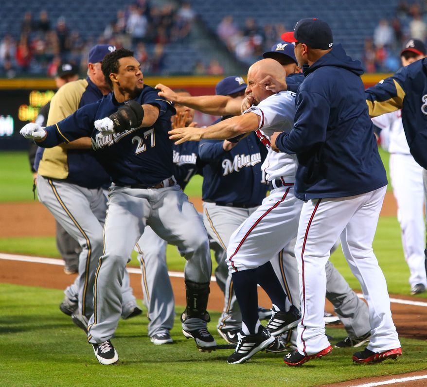 Milwaukee Brewers Carlos Gomez, left, and Atlanta Braves Reed Johnson, right, exchange blows when both benches clear following a home run by Gomez in the first inning of a baseball game Wednesday, Sept. 25, 2013 in Atlanta. (AP Photo/Atlanta Journal-Constitution, Curtis Compton)