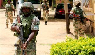 ** FILE ** Nigerian soldiers stand guard in Maiduguri, Nigeria, June 6, 2013. (Associated Press)