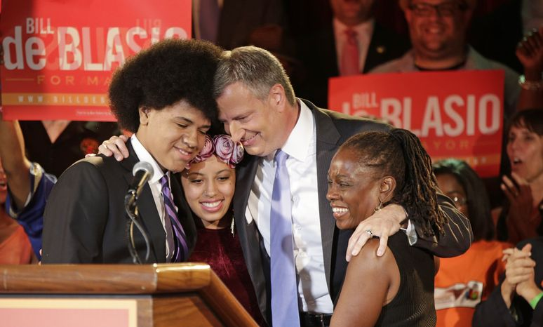 ** FILE ** In this Sept. 10, 2013, file photo, New York Democratic mayoral hopeful Bill de Blasio embraces his son Dante, left, daughter Chiara, second from left, and wife Chirlane McCray, right, at his election headquarters after polls closed in the city's primary election in New York. Dante, 16, whose large, perfectly coiffed afro is hard to miss at campaign stops and in a TV spot as dad runs for New York City mayor. (AP Photo/Kathy Willens, File)