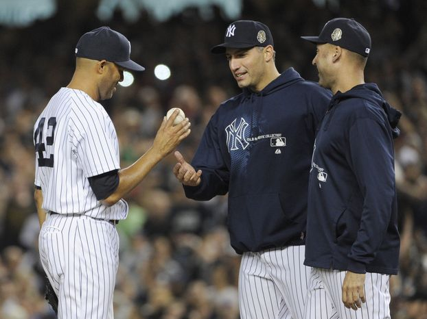 New York Yankees relief pitcher Mariano Rivera, left, hands the ball to Andy Pettitte as Derek Jeter, right, watches during the ninth inning of a baseball game against the Tampa Bay Rays on Thursday, Sept. 26, 2013, at Yankee Stadium in New York. The Yankees defeated the Rays 4-0 in Rivera's final home game with the team. (AP Photo/Bill Kostroun)