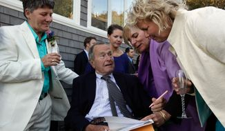 In this Sept. 21, 2013, photo, former President George H.W. Bush, seated center, prepares to sign the marriage license of longtime friends Helen Thorgalsen, right, and Bonnie Clement, left, in Kennebunkport, Maine, as officiant Nancy Sosa, third right, and Helen's daughter Lindsey, rear, look on. Bush was an official witness at the same-sex wedding, his spokesman said Wednesday, Sept. 25, 2013. (AP Photo/Susan Biddle)