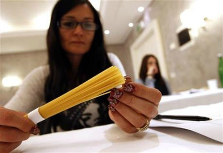 ** FILE ** A woman touches pasta in a hotel conference room in Rome, May 18, 2012. (Associated Press)