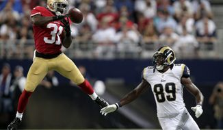 San Francisco 49ers safety Donte Whitner deflects a pass intended for St. Louis Rams tight end Jared Cook before Cook caught the ball for an 18-yard gain during the second quarter of an NFL football game Thursday, Sept. 26, 2013, in St. Louis. (AP Photo/Tom Gannam)