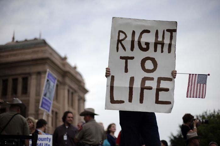 **FILE** A man holds a sign during an anti-abortion rally at the Texas Capitol in Austin on July 8, 2013. (Associated Press)