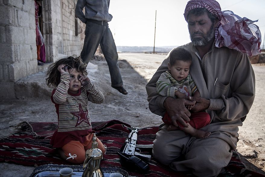 A Free Syrian Army fighter holds his son outside their home in Habit village, the Syrian central province of Hama, Wednesday, Sep. 25, 2013. (AP Photo)