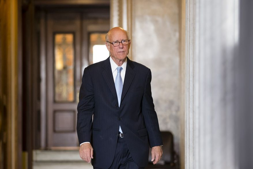 """**FILE** Sen. Pat Roberts, Kansas Republican, leaves the Senate after assisting fellow Republican Sen. Ted Cruz of Texas with his overnight fight on the floor against the Affordable Care Act, popularly known as """"Obamacare,"""" at the U.S. Capitol in Washington on Sept. 25, 2013. Cruz and other conservative Republicans were trying to delay a must-pass spending bill. (Associated Press)"""