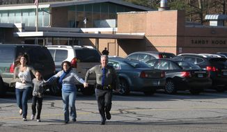 ** FILE ** A police officer leads two women and a child from the Sandy Hook Elementary School in Newtown, Conn., where a gunman opened fire, killing 26 people, including 20 schoolchildren. (AP Photo/Newtown Bee, Shannon Hicks)