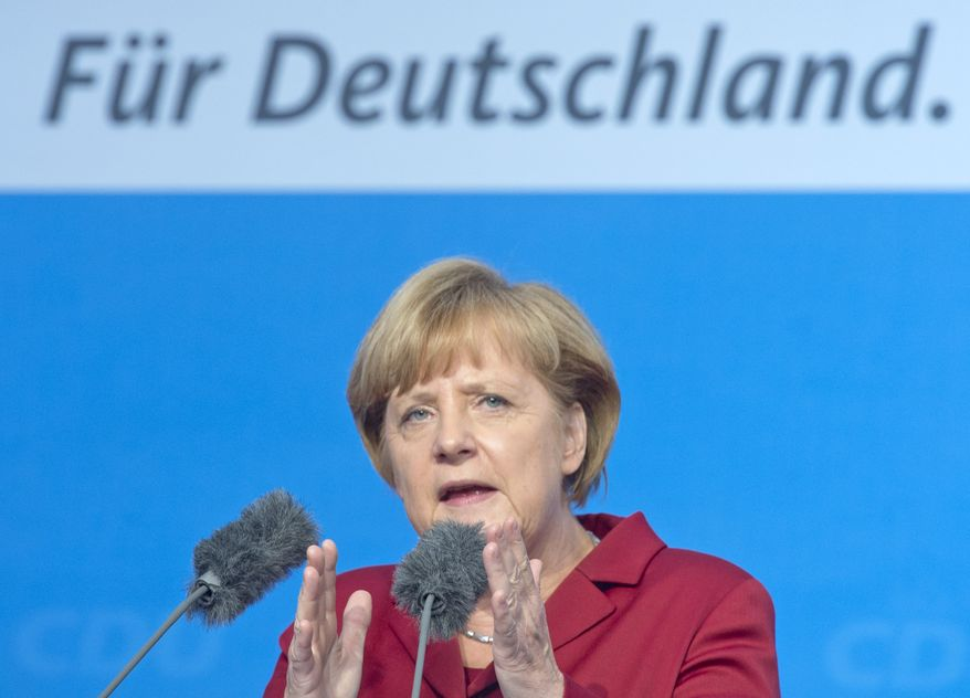 German Chancellor Angela Merkel gestures during her speech at an election campaign event her  German Christian Democratic Union (CDU) in Fulda, Germany, on Thursday, Sept. 19, 2013. Words in background  read: 'For Germany'.  General elections are scheduled for Sunday Sept. 22, 2013. (AP Photo/Jens Meyer)